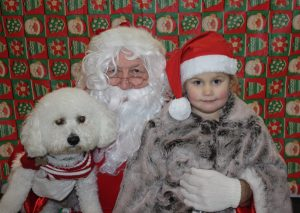 Santa Claus with a child and small white dog