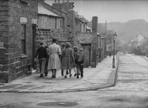 A vintage black and white photograph of a family walking down the street