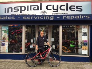 Man with a red bicycle outside of Inspiral Cycles shop