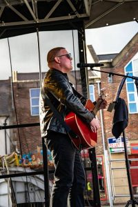 Kevin Baldam singing and playing acoustic guitar on stage
